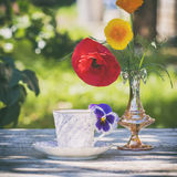 Porcelain cup of tea and beautiful spring flowers in vase on a wooden table in the garden. Summer party. Royalty Free Stock Photography