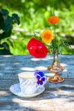 Porcelain cup of tea and beautiful spring flowers in vase on a wooden table in the garden. Summer party. Stock Photography