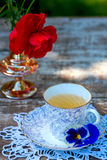 Porcelain cup of tea and beautiful spring flowers in vase on a wooden table in the garden. Summer party. Stock Photos