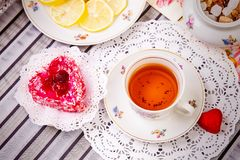 Porcelain cup of tea with lemon and sweets Royalty Free Stock Photos
