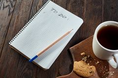 Cup of tea with cookies, workbook and a pencil on a wooden background, top view. A porcelain cup of tea with tasty chocolate chips cookies, empty workbook and Royalty Free Stock Photography