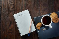 Cup of tea with cookies, workbook and a pencil on a wooden background, top view. A porcelain cup of tea with tasty chocolate chips cookies, empty workbook and Royalty Free Stock Image