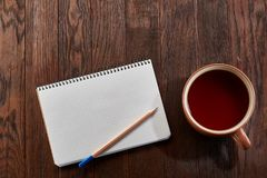 Cup of tea with cookies, workbook and a pencil on a wooden background, top view. A porcelain cup of tea with tasty chocolate chips cookies, empty workbook and Royalty Free Stock Images