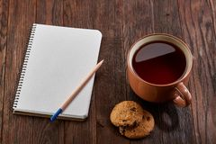 Cup of tea with cookies, workbook and a pencil on a wooden background, top view. A porcelain cup of tea with tasty chocolate chips cookies, empty workbook and Stock Image