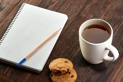 Cup of tea with cookies, workbook and a pencil on a wooden background, top view. A porcelain cup of tea with tasty chocolate chips cookies, empty workbook and Royalty Free Stock Photos