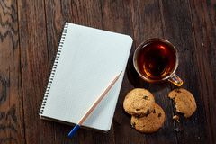 Cup of tea with cookies, workbook and a pencil on a wooden background, top view. A porcelain cup of tea with tasty chocolate chips cookies, empty workbook and Royalty Free Stock Photo