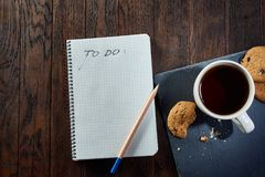 Cup of tea with cookies, workbook and a pencil on a wooden background, top view. A porcelain cup of tea with tasty chocolate chips cookies, empty workbook and Stock Images