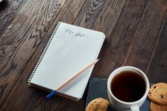 Cup of tea with cookies, workbook and a pencil on a wooden background, top view. A porcelain cup of tea with tasty chocolate chips cookies, empty workbook and Stock Photo