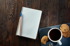 Cup of tea with cookies, workbook and a pencil on a wooden background, top view. A porcelain cup of tea with tasty chocolate chips cookies, empty workbook and Stock Photography