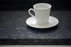 Porcelain cup and white saucer in contrast with black granite. Background Royalty Free Stock Photos
