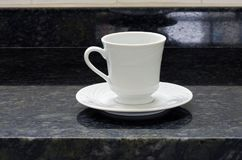 Porcelain cup and white saucer in contrast with black granite. Background Stock Image