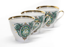 Porcelain cups with a green pattern and a gold border in a row Stock Photos