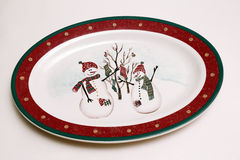 Porcelain dining plate with image of two snowmen in hats and sca Royalty Free Stock Image