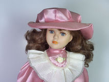 A porcelain doll with big beautiful eyes. In an elegant hat with Stock Photo