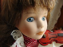 Porcelain doll with blue eyes. Playing the violin Stock Image