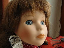 Porcelain doll with blue eyes. Playing the violin royalty free stock photo
