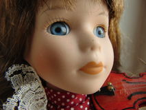 Porcelain doll with blue eyes. Playing the violin stock images