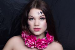 Porcelain doll with broken face. Art make up vintage porcelain doll with broken face, black cracked pieces lines. Pink roses flowers necklace. New conceptual Stock Photos