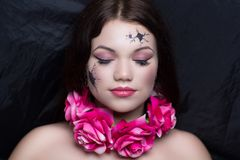 Porcelain doll with broken face. Art make up vintage porcelain doll with broken face, black cracked pieces lines. Pink roses flowers necklace. New conceptual Stock Images