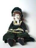 Porcelain doll. Female porcelain doll dressed in green velvet sitting up against white background Royalty Free Stock Photos