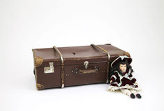 Porcelain doll next to old shabby suitcase Royalty Free Stock Photos