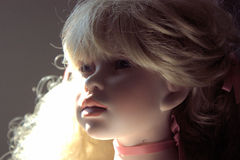 Porcelain doll Portrait. Blonde Hair porcelain doll with blue eyes and shadow on the left side of the face.  She is looking up slightly to the right. Portrait Stock Photo