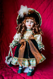 Porcelain doll. On a red background Royalty Free Stock Photo