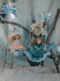 Porcelain dolls on swings photo. Royalty Free Stock Photo