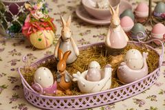Porcelain Easter bunnys or rabbits with eggs on the table royalty free stock photo
