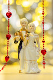 Porcelain figures of boy and girl with background beads. Porcelain figures of a boy and a girl in the costumes of the last century on a red background beads and Stock Images
