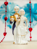 Porcelain figures of boy and girl with background beads and hear. Porcelain figures of a boy and a girl in the costumes of the last century, red beads on a blue Stock Photos