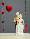 Porcelain figures of boy and girl with background heart. Porcelain figures of a boy and a girl in the costumes of the last century on a red background heart and Royalty Free Stock Image