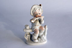 Porcelain figurine of a boy. Serial porcelain figurine of a boy playing a flute from the decor store royalty free stock images