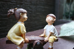 Porcelain Figurine Of Children On A See-Saw. Porcelain figurine of a smiling young girl and boy on a see-saw Stock Image