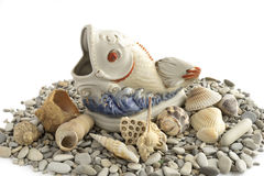 Porcelain fish and different shells on a white background. Royalty Free Stock Photography