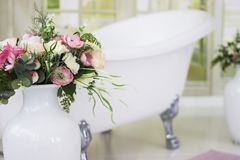 Porcelain freestanding bath in designed white bathroom. White luxurious bath, a bouquet of flowers in a large vase. Still life or. Compass. Retro bath, bouquet stock photo