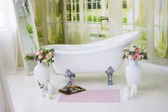 Porcelain freestanding bath in designed white bathroom. White luxurious bath, a bouquet of flowers in a large vase. Still life or. Compass. Retro bath, bouquet stock photos