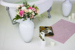 Porcelain freestanding bath in designed white bathroom. White luxurious bath, a bouquet of flowers in a large vase. Still life or royalty free stock image