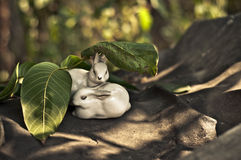 Porcelain hares under green leaves Royalty Free Stock Image