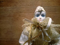 A porcelain harlequin puppet. On a wooden background Royalty Free Stock Photo