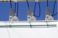 Porcelain insulators of high-voltage substation on blue sky stock image
