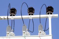 Porcelain insulators of high-voltage substation on blue sky stock photos