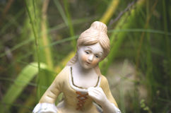 Porcelain lady. Vintage sculpture - porcelain female talking in a garden Royalty Free Stock Images