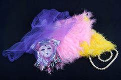 Porcelain mask lay on feathers covered by violet netting near pearl necklace on black background Stock Photo