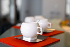 Porcelain modern cups with stainless steel saucers and spoons on Stock Photo