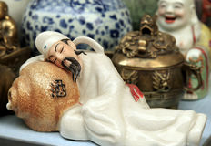 Porcelain person art. This is an interesting scene, he has gotten drunk, at the same time falls asleep, actually is also holding the liquor demijohn. The Royalty Free Stock Photos
