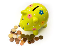 Porcelain piggy bank and coins Royalty Free Stock Photos