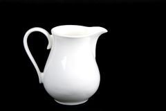 Porcelain pitcher. White porcelain creamer pitcher isolated on black Stock Image