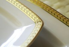 Porcelain plate. Empty white porcelain plate with gold pattern royalty free stock photo
