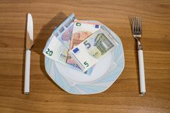 Porcelain plate full of euro on a wood table. Composition stock photos